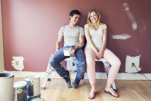 Happy couple sitting on stool against wall at home - CAVF37023