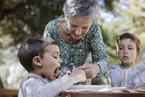 Senior woman feeding breakfast to grandson at yard - CAVF37125