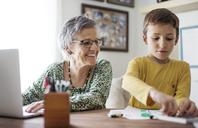 Happy senior woman looking at grandson choosing crayons at home - CAVF37131