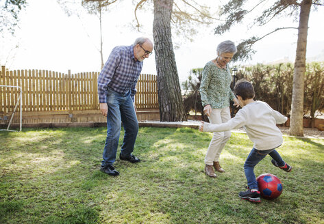 Cheerful grandparents and grandsons playing soccer at yard - CAVF37143