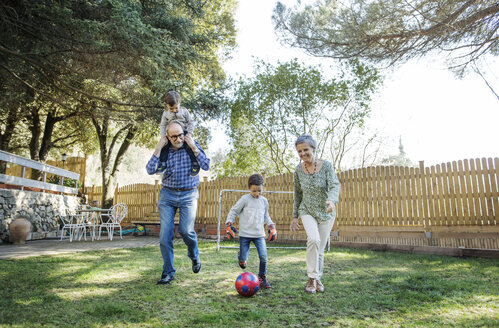 Full length of grandparents and grandsons playing soccer at yard - CAVF37146
