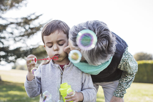 Senior woman kissing grandson playing with blowing bubbles in park - CAVF37158