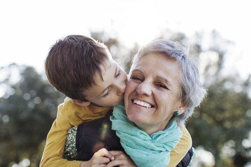 Loving grandson kissing grandmother in park - CAVF37167