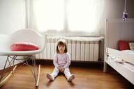 Thoughtful girl sitting on hardwood floor in bedroom - CAVF37170