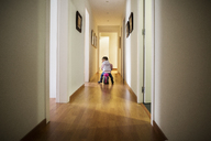 Rear view of girl sitting on bicycle in corridor at home - CAVF37173