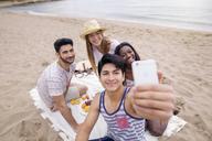 Friends taking selfie while enjoying picnic on beach - CAVF37200