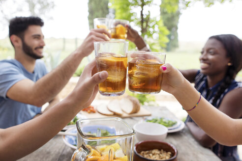 Friends toasting iced tea glasses at outdoor table - CAVF37221