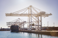 Low angle view of cranes at commercial dock against clear sky - CAVF37503