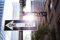 Low angle view of directional sign against buildings in city - CAVF37506