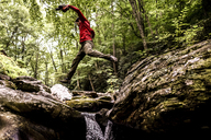 Low angle view of hiker leaping over rocks in forest - CAVF37536