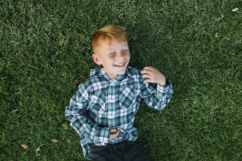 Overhead view of happy boy lying on grassy field at park - CAVF37593