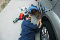 High angle view of father teaching son to repair car at driveway - CAVF37614
