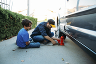 Father teaching son to use car jack while sitting at driveway - CAVF37620