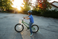 Boy wearing cycling helmet while riding bicycle during sunset - CAVF37623