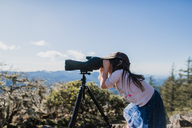 Side view of girl looking through telescope while standing against sky - CAVF37632