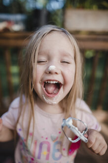 Playful girl with eyes closed laughing while holding whisk - CAVF37677