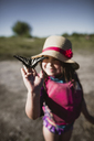 Girl holding butterfly while standing on field during summer - CAVF37686