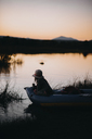 Girl sitting in inflatable raft on lake against clear sky during sunset - CAVF37689