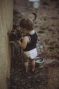 High angle view of boy giving water to dog from faucet while holding cup - CAVF37713