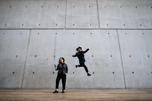 Man in mid-air while woman using phone against wall - CAVF37734
