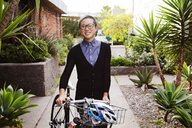 Portrait of happy businesswoman with bicycle standing at park - CAVF37764