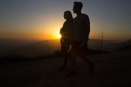Silhouette couple standing on mountain against sky during sunset - CAVF37806