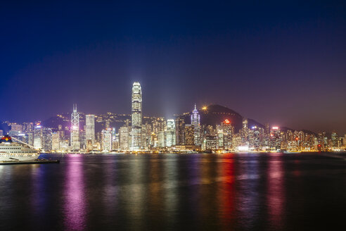 Victoria harbour against illuminated Two International Finance Center and buildings in city at night - CAVF37914