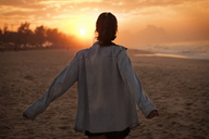 Young woman looking at sunset on beach - CAVF37926