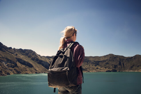 Rear view of female hiker against lake and mountains - CAVF37947