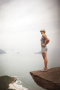Woman standing on cliff and looking at sea in fog - CAVF37956