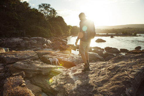 Side view of male hiker walking on rocky lakeshore during sunset - CAVF37977