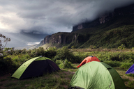 Tents on green mountain against cloudy sky - CAVF37980