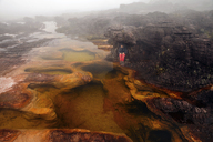 High angle view of woman sitting on rock by lake in foggy weather - CAVF37986