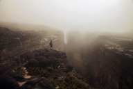 Mid distance of man standing on cliff in foggy weather - CAVF37989