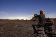 Rear view of male hiker photographing while sitting on rock against clear blue sky - CAVF37995