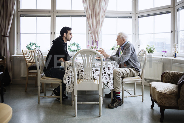 Side view of man communicating with caretaker at dining table - MASF03259 - Maskot ./Westend61