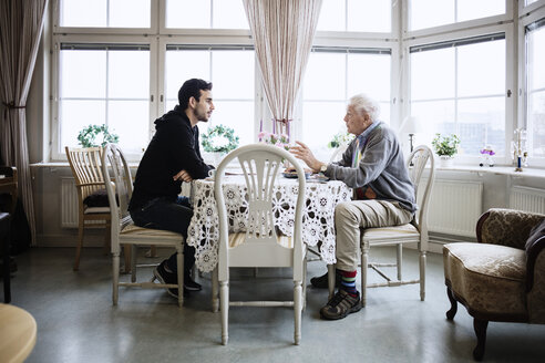 Side view of man communicating with caretaker at dining table - MASF03259