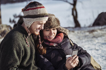 Smiling couple using smart phone while relaxing on snow covered field - MASF03265