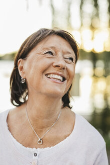 Thoughtful senior woman looking up and smiling outdoors - MASF03304