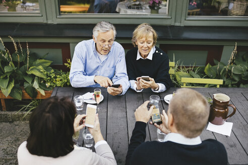 Two senior couples using mobile phones at table of outdoor restaurant - MASF03310