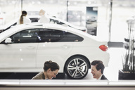 Smiling women discussing by car at showroom - MASF03313
