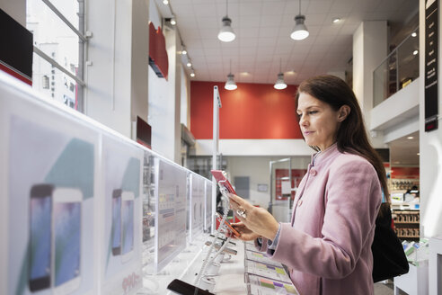 Side view of woman using smart phone in store - MASF03325