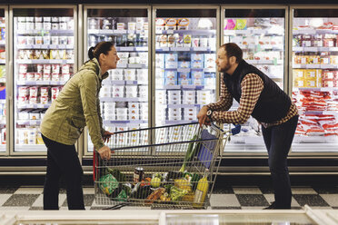 Side view of couple talking while leaning on shopping cart at refrigerated section - MASF03343