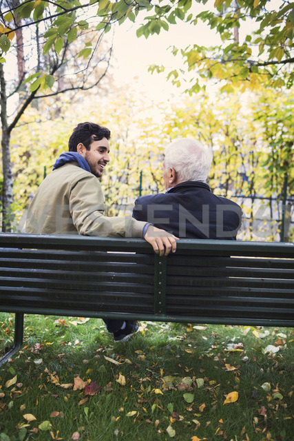 Rear view of caretaker looking at senior man while sitting on bench at park - MASF03349 - Maskot ./Westend61