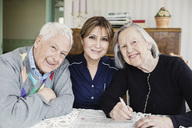 Portrait of smiling caretaker and senior people solving crossword puzzle at nursing home - MASF03352