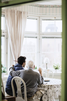 Rear view of caretaker with elderly man in nursing home - MASF03355