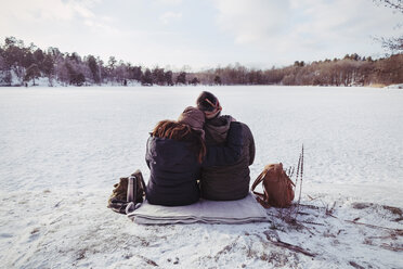 Rear view of male and female hiker sitting on snow covered field - MASF03358