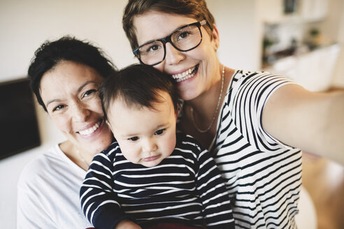 Portrait of smiling lesbian couple with toddler at home - MASF03379