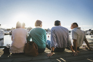 Rear view of two senior couples sitting on pier against clear sky - MASF03403