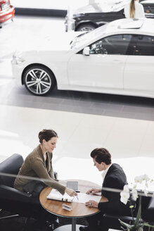 Salesperson explaining document to customer at car showroom - MASF03406